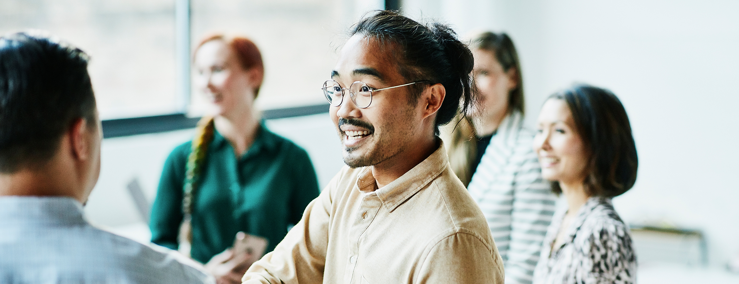 Man in glasses and man bun shaking hands with colleague